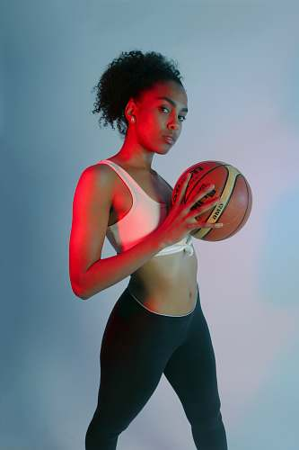 person standing woman wearing pink sports bra holding basketball hair