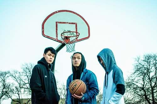 people three men wearing hoodie near basketball hoop person