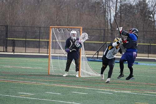 person three people playing lacrosse on green field near goal net people