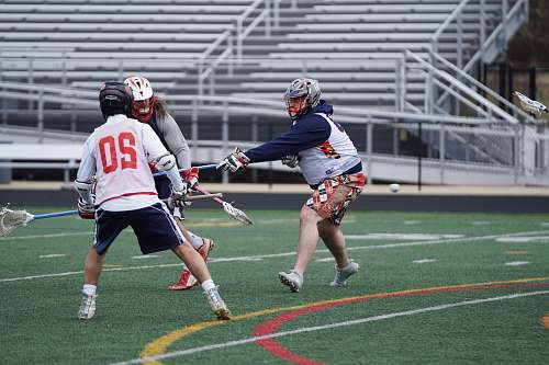 apparel three person playing lacrosse on field during daytime clothing