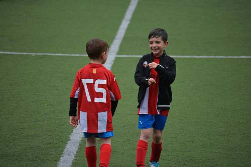 person two boy standing on soccer field people
