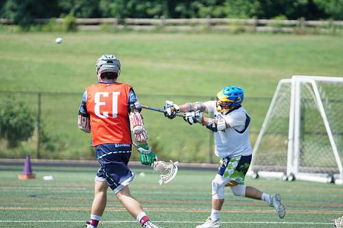 person two men playing lacrosse during daytime apparel