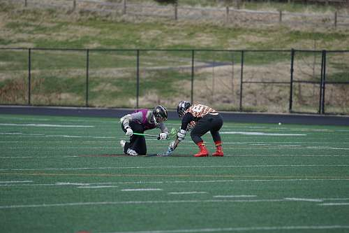 person two men playing lacrosse on field people