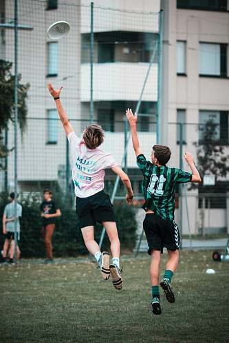 person two men reaching frisbee while jumping people
