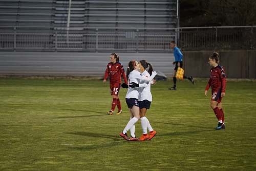 person two sports players hugging in field people