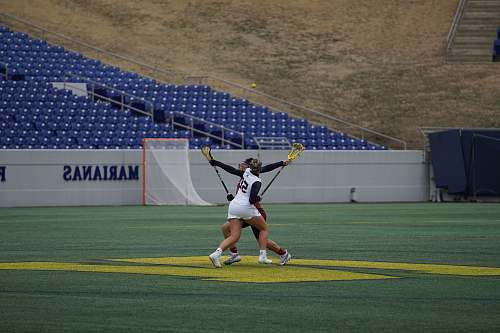 person two women holding lacrosse stick people