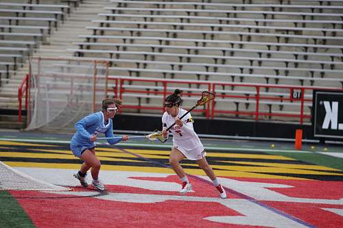 person two women playing lacrosse during daytime apparel