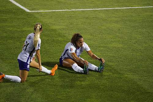 person two women soccer players stretching legs on lawn people
