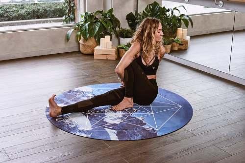 floor woman doing yoga on round blue yoga mat flooring
