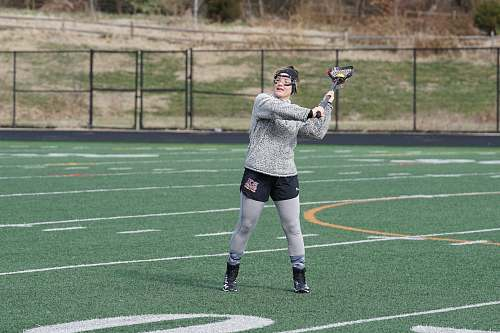person woman in grey sweat shirt playing lacrosse during daytime people