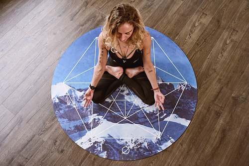 person woman meditating in center of round mat floor