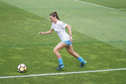 person woman on football field dribbling soccer ball at daytime people