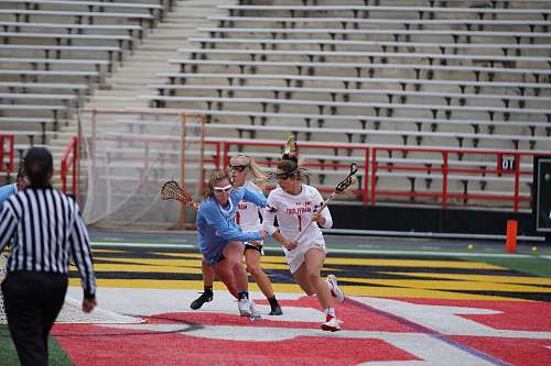 person woman playing lacrosse on stadium sphere