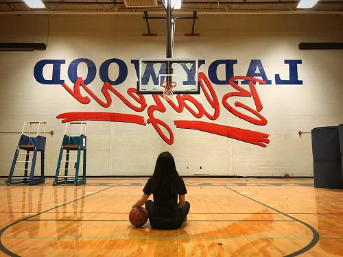 person woman sitting in basketball court floor people