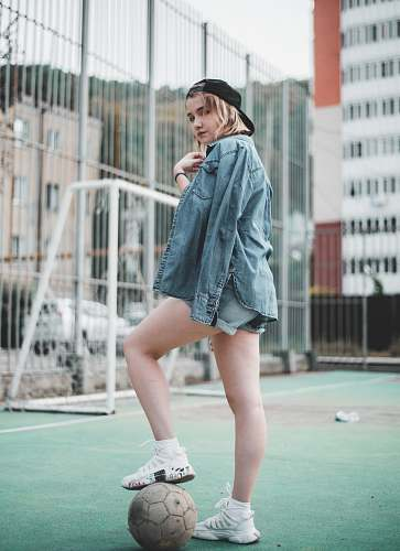 apparel woman wearing blue denim jacket standing and stepping right foot on white soccer ball in green field during daytime clothing