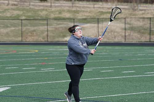 person woman wearing gray jacket standing and holding lacrosse stick on green field at daytime racket