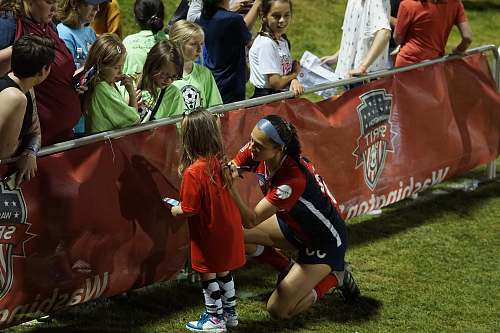 person woman wearing red and black jersey helping little girl people
