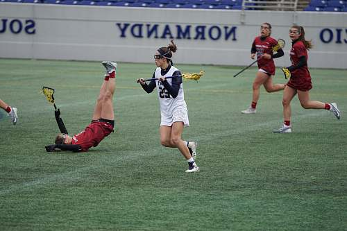 person women playing lacrosse during daytime people