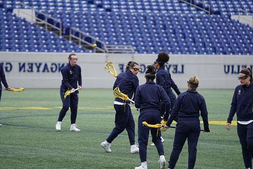 person women playing lacrosse on field during daytime people