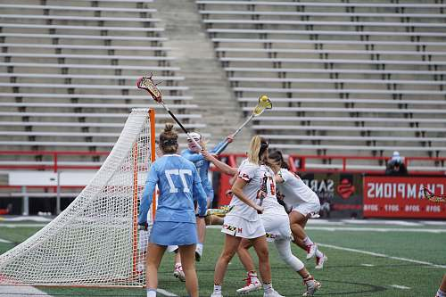 person women playing lacrosse outside apparel