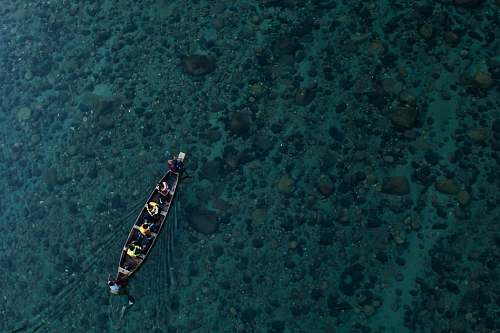 water aerial photo of canoe on calm water with people aerial view