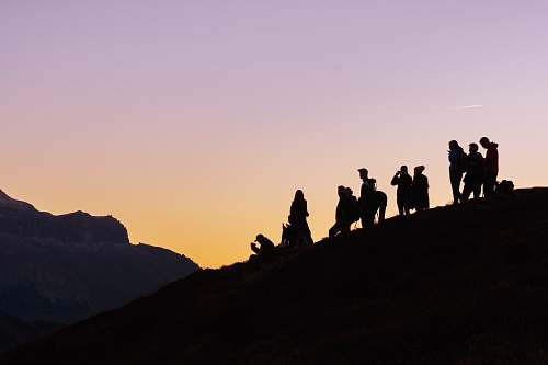 sunset silhouette of group of people on hill silhouette