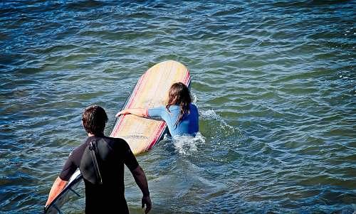 ocean woman holding surfboard near man standing on body of water sea