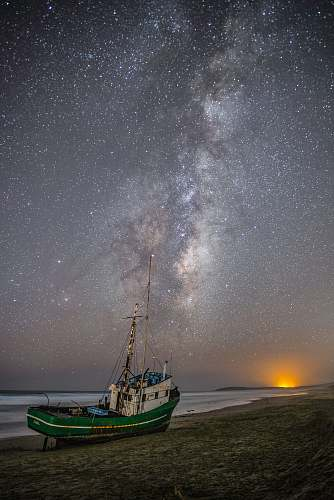 astronomy green and white fishing boat on gray sand under white and gray sky milky way