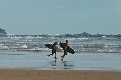 water man and woman holding surfboards running near seashore under blue and white skies during daytime nature