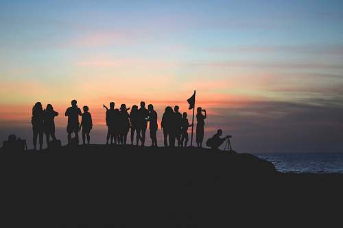 horizon silhouette photography of people gathered together on cliff sky