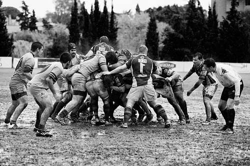 black-and-white grayscale photography of men playing rugby on muddy land sport