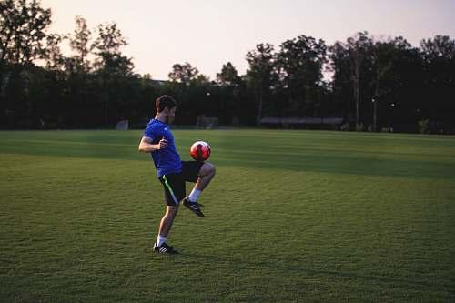 human man juggling ball on grass field person