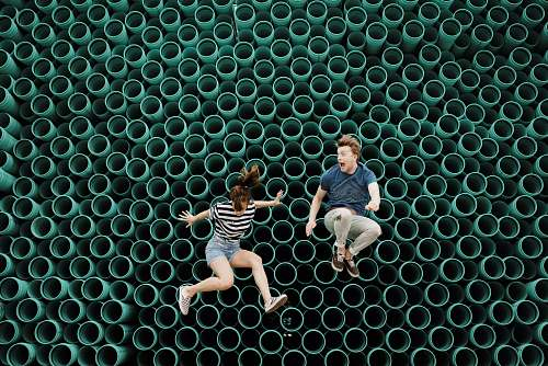 pattern minimalist photography of man and woman jumping in front of tube wall siloam springs