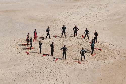 group people standing forming a circle during daytime beach