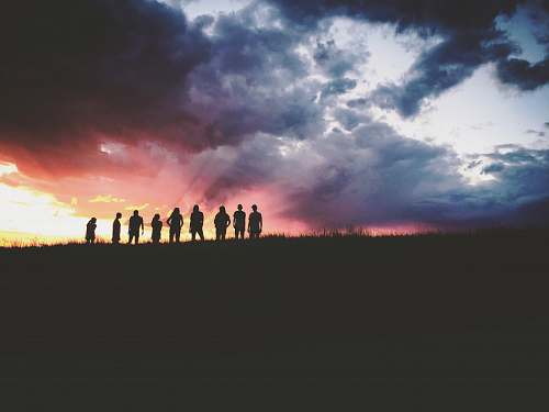outdoors silhouette of nine persons standing on the hill sky