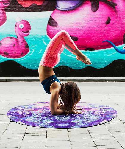 yoga woman doing acrobats on purple mat during daytime fitness