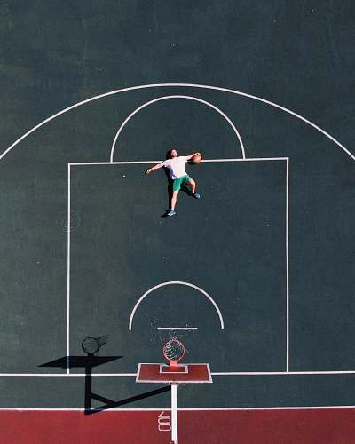 human aerial photography of man lying on basketball court people