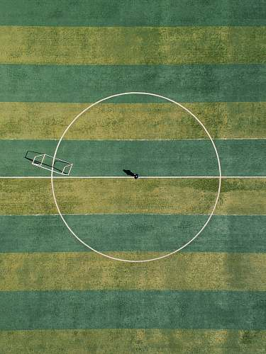 sport aerial view of person standing between circle field during daytime football field