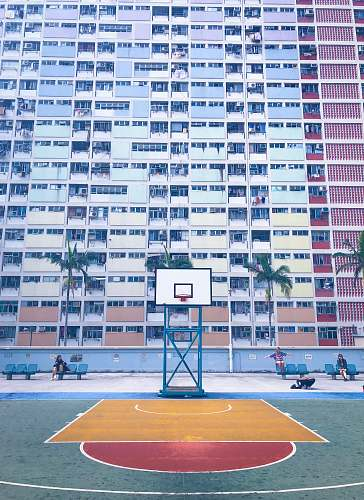 human basketball court in front of concrete high-rise building during daytime people