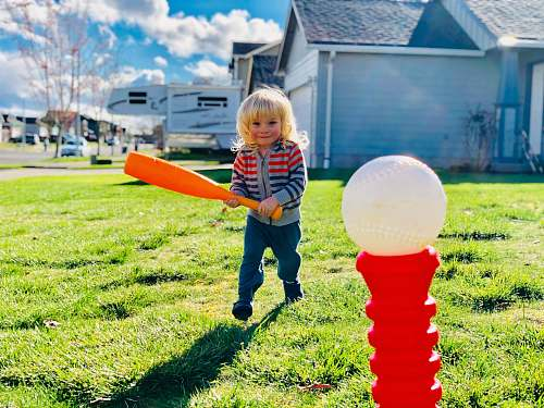 human boy holding orange bat walking toward red and white plastic pole toy people