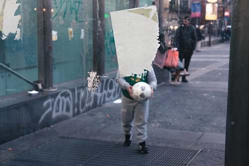 human boy holding white soccer ball pedestrian