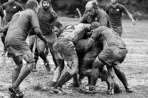 people grayscale photography of group of people playing rugby on muddy field black-and-white