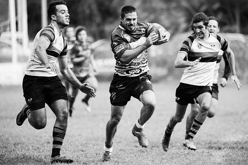 people grayscale photography of men playing rugby black-and-white