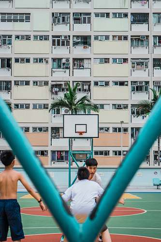 human group of people playing basketball during daytime people