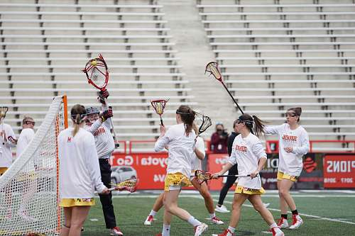 human group of people playing lacrosse on field apparel