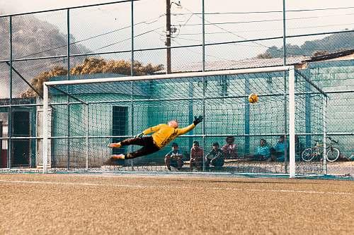 sport man jump about to hold ball near net football