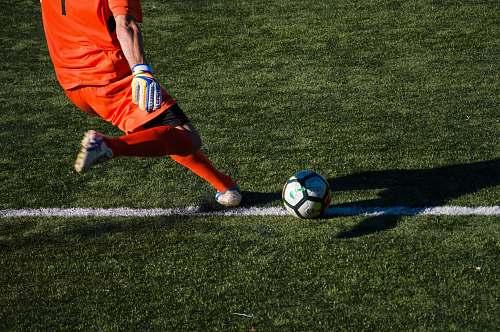 human man kicking soccer ball on field people