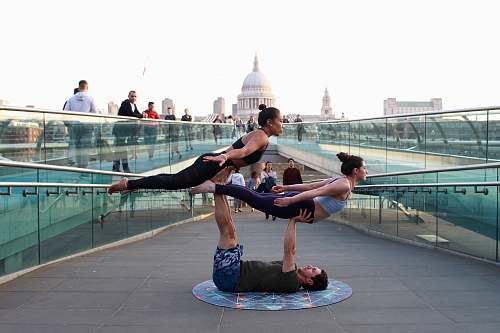 human man on his back supporting two women during daytime people