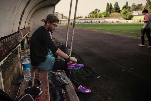human man tying his shoes while sitting on bench bottle