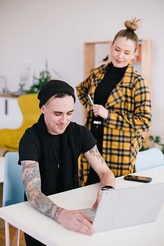 human man using laptop beside woman holding pen skin